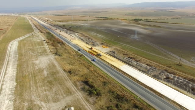 aerial: construction of new highways in countryside - road construction stock videos and b-roll footage
