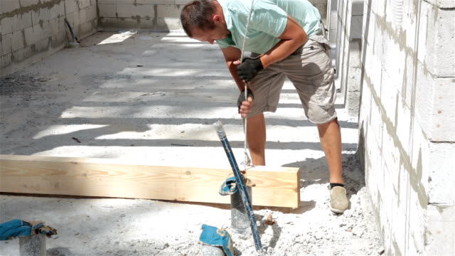 construction of the roof. builder lifts the wooden beam to the roof. - roof beam stock videos & royalty-free footage