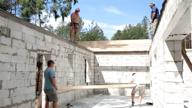 construction of the roof. builders lift the wooden beam to the roof. - roof beam stock videos & royalty-free footage