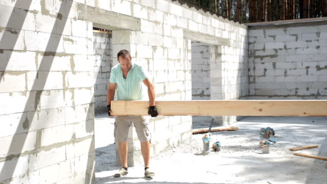construction of the roof. builders lift the wooden beam to the roof. - timber stock videos and b-roll footage