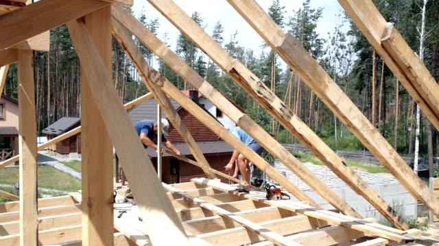 屋根の建設。屋根葺き職人は、屋根に取り組みます。 - 住宅開発点の映像素材/bロール