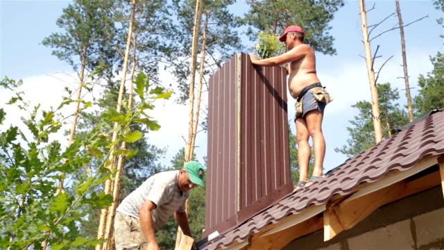 construction of the roof. roofers work on the roof. - drill stock videos & royalty-free footage