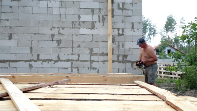 construction of the roof. the builder cleans the beam from the bark with a chainsaw. - roof beam stock videos & royalty-free footage