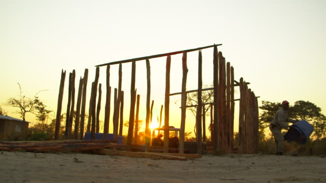 Construction of wooden shack in Angola during sunset