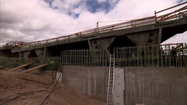 vídeos y material grabado en eventos de stock de construction on a bridge proceeds above a walled excavation. - pared de cemento