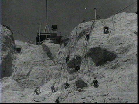 Construction on Lincoln's face on Mount Rushmore begins / View from below of men working on the monument / Gutzon Borglum and his men working / Men...