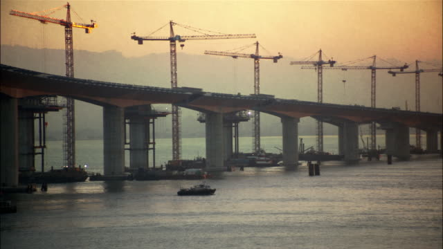 construction on the eastern span of the san francisco-oakland bay bridge with small ship crossing san francisco bay / san francisco - san francisco oakland bay bridge stock videos & royalty-free footage
