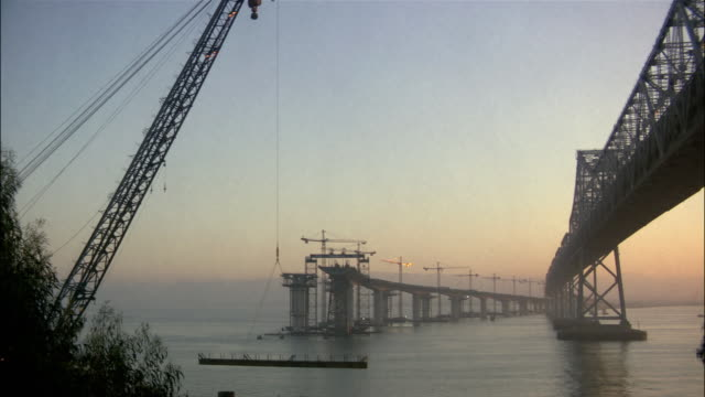 construction on the eastern span of the san francisco-oakland bay bridge with crane operating lift / san francisco - san francisco oakland bay bridge stock videos and b-roll footage