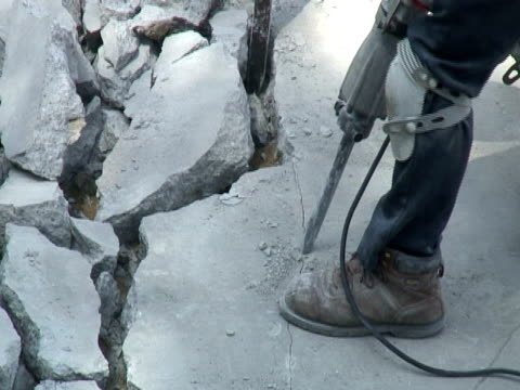 construction: pneumatic drill / jackhammer breaks concrete - pneumatic drill stock videos & royalty-free footage