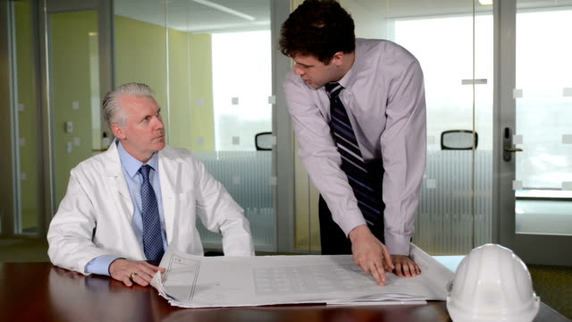 construction professional discusses blueprint plans with doctor - materiale cartaceo video stock e b–roll