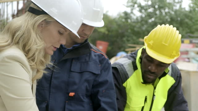 stockvideo's en b-roll-footage met construction project team working on a blueprint at construction site - hoofddeksel