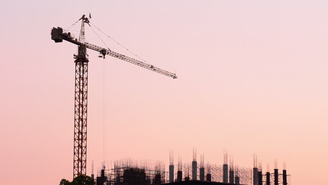 stockvideo's en b-roll-footage met construction silhouette at sunset - bouwmachines