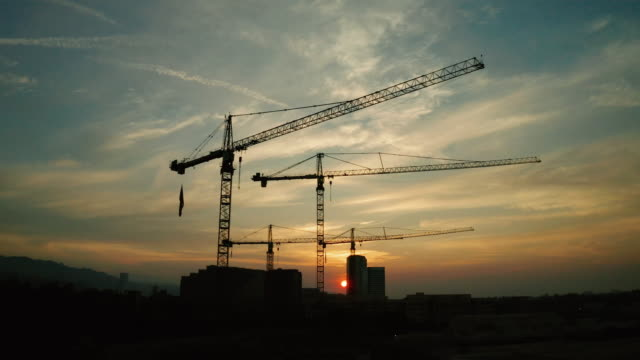 vídeos de stock e filmes b-roll de construction site - aerial view of cranes at sunset - guindaste maquinaria de construção