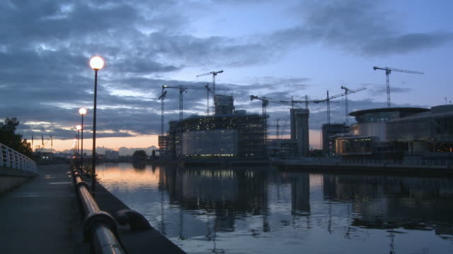 ws, construction site at salford quays at dusk, view across canal, manchester, england - salford quays stock videos & royalty-free footage