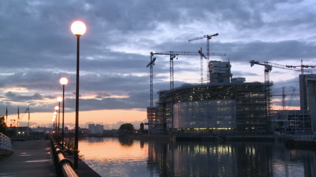 zo, ws, construction site at salford quays at dusk, view across canal, manchester, england - salford quays stock videos & royalty-free footage