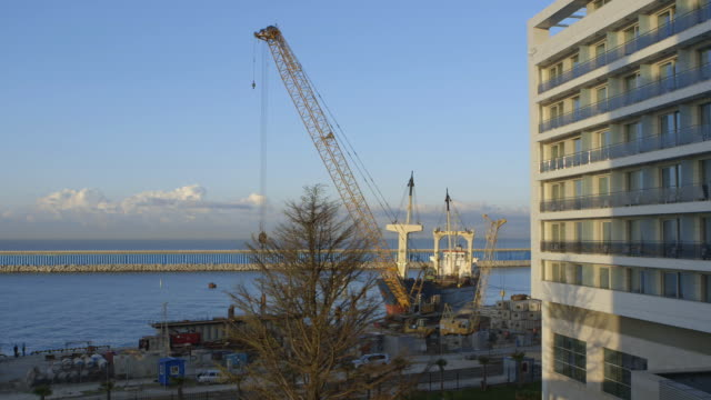 Construction Site On Black Sea Sline Tall Cranes Cement Blocks Freight Ship In Water Midrise Building