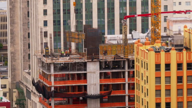 construction site on skyscraper in downtown miami. formwork panel haning from crane. wide shot - spoonfilm stock-videos und b-roll-filmmaterial