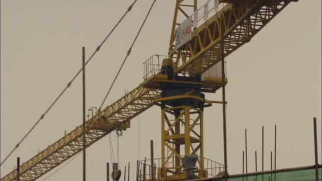MS TD Construction site with crane and workers behind safety netting / Shenzhen, Guangdong, China