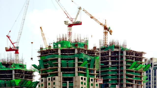 construction site with many crane working zoom out - building activity stock videos & royalty-free footage