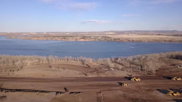 a construction site with tractors by a lake in littleton colorado - road construction stock videos and b-roll footage