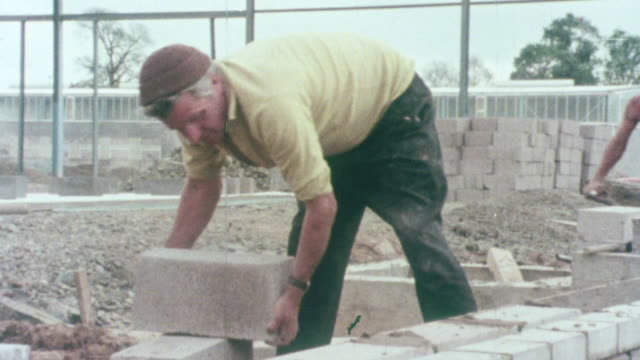 1976 montage construction site workers performing concrete, masonry and plaster work / united kingdom - mattone video stock e b–roll