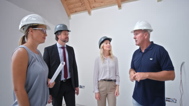 construction supervisor and female architect talking to the man and woman inside their future home - caucasian appearance stock videos & royalty-free footage
