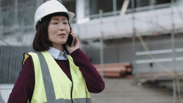 construction supervisor speaking on phone - 建設作業員点の映像素材/bロール