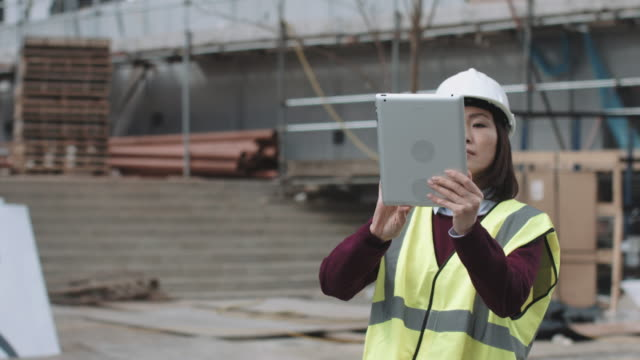 construction supervisor taking picture with digital tablet of project development - 労働者点の映像素材/bロール
