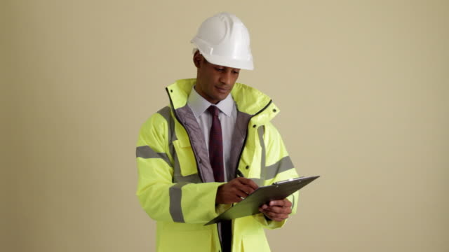 MWS construction supervisor using clipboard looking up and smiling at camera