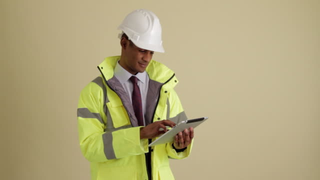 mws construction supervisor using tablet looking up and smiling at camera - giacca e cravatta video stock e b–roll