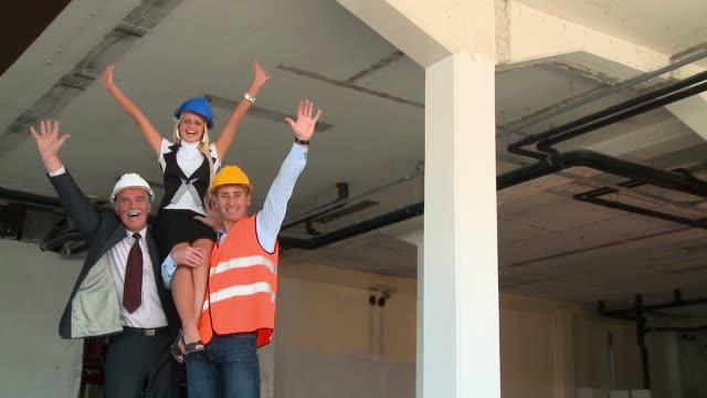 hd crane: construction team - bära bildbanksvideor och videomaterial från bakom kulisserna