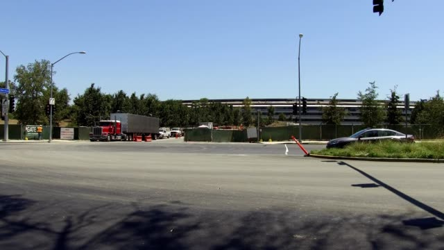 A construction truck exits Apple Parkway and turns onto Wolfe Street at the Apple Park known colloquially as The Spaceship the new headquarters of...