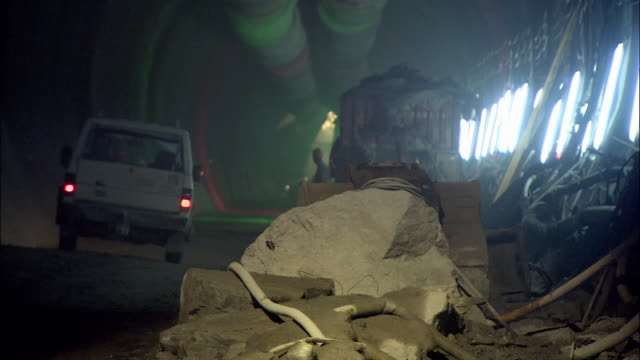ws construction vehicle passing worker in tunnel / amsteg, uri canton, switzerland - construction vehicle stock videos & royalty-free footage