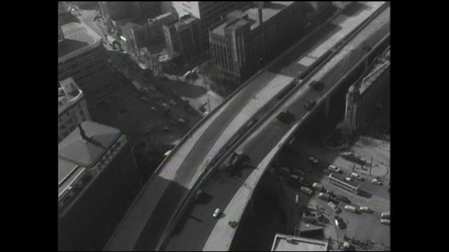 Construction vehicles are on the Tokyo Metropolitan Expressway project as local traffic moves beneath on a city street.