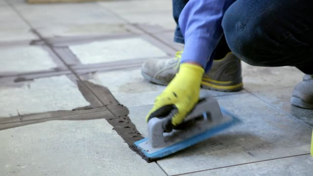 Construction work with floor ceramic tiles.