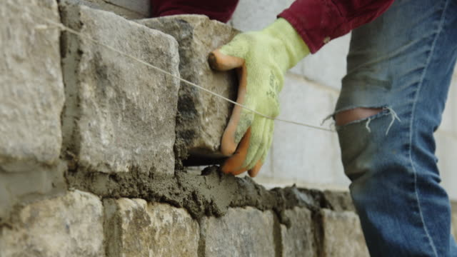 Construction Worker Adding Block to Wall
