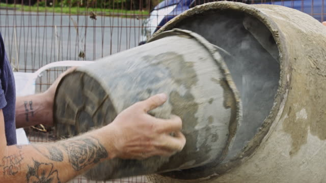 vídeos y material grabado en eventos de stock de trabajador de la construcción añadiendo polvo de cemento al mezclador - cement mixer