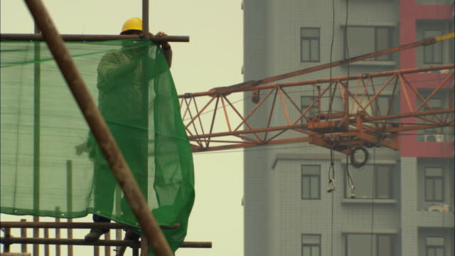 WS Construction worker affixing safety netting on scaffolding / Shenzhen, Guangdong, China