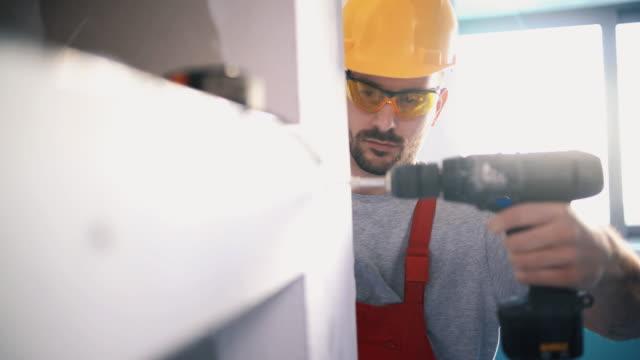 Construction worker assembling a drywall.