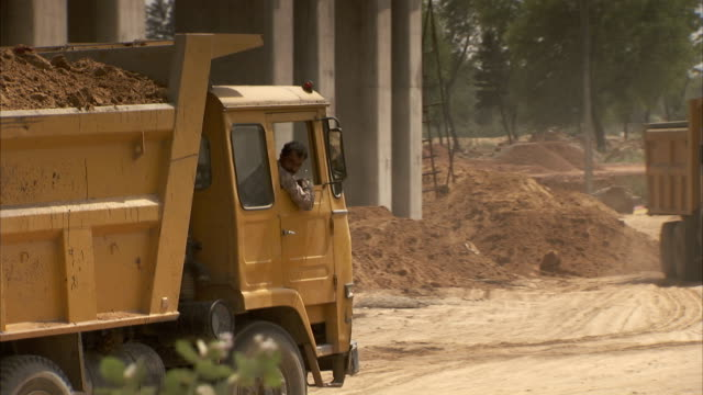 a construction worker backs up a heavy dump truck across the construction site on the road to jaipur, india. available in hd. - baustelle stock-videos und b-roll-filmmaterial