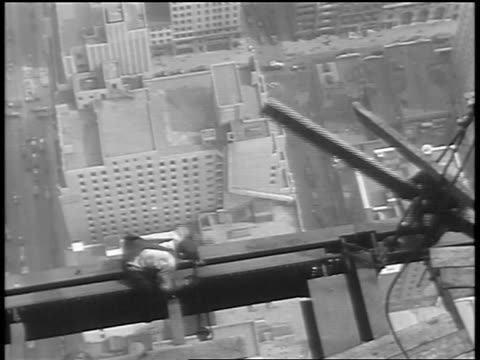 OVERHEAD construction worker carrying plank walking on girder of Empire State Building