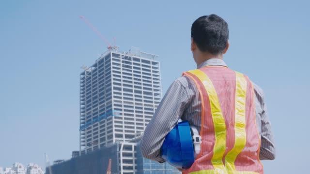 建設労働者の背景にクレーンで所在地を確認 - 工事点の映像素材/bロール