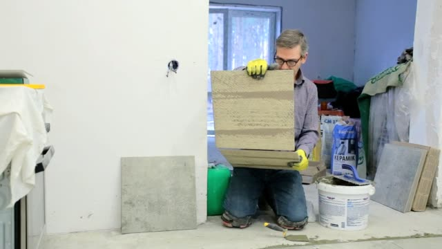 Construction worker chooses a ceramic tile.