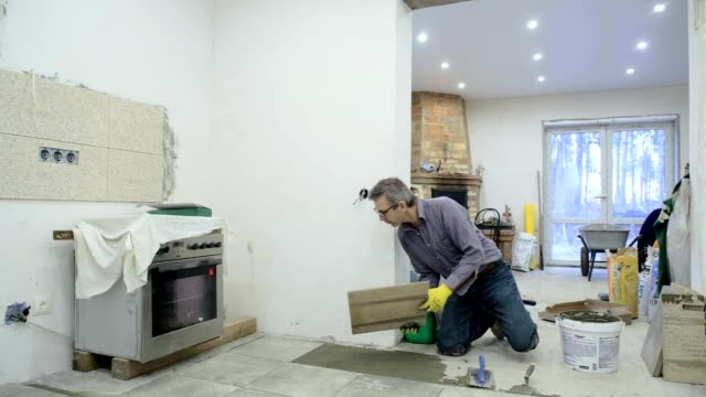 Construction worker chooses and puts ceramic tiles on the floor.