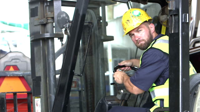 Construction worker climbing onto forklift