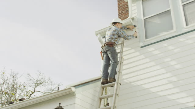 construction worker climbing up a ladder and doing work on a residential home - ladder stock videos & royalty-free footage
