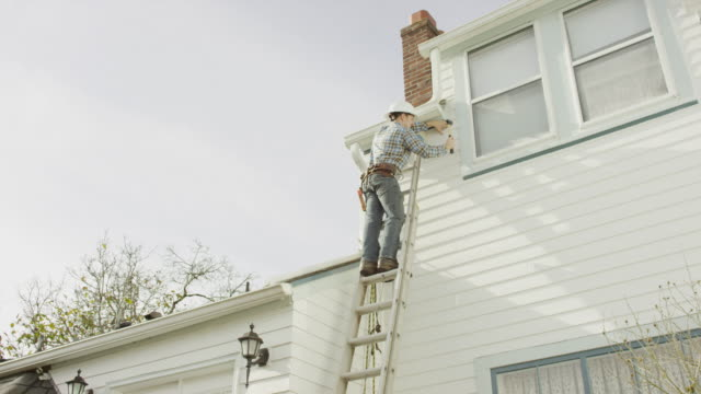 construction worker climbing up a ladder and doing work on a residential home - ladder stock videos and b-roll footage