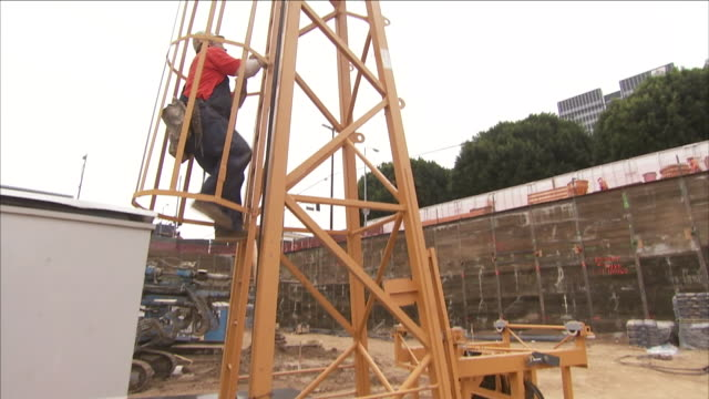a construction worker climbs a cherry picker. - cherry picker stock videos & royalty-free footage