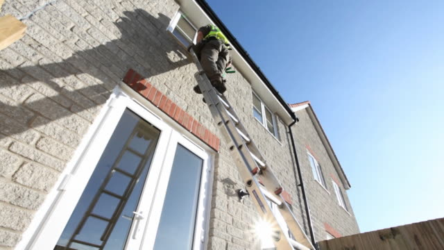 a construction worker climbs down a ladder leaning against the exterior wall of a new house in the united kingdom. - ladder stock videos & royalty-free footage