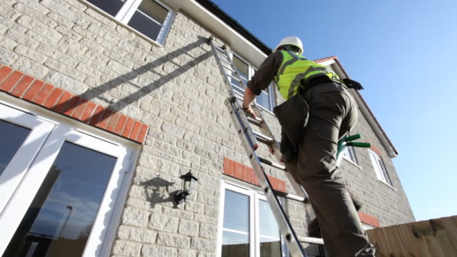 stockvideo's en b-roll-footage met a construction worker climbs up a ladder outside the exterior wall of a new house in the united kingdom. - ladder gefabriceerd object